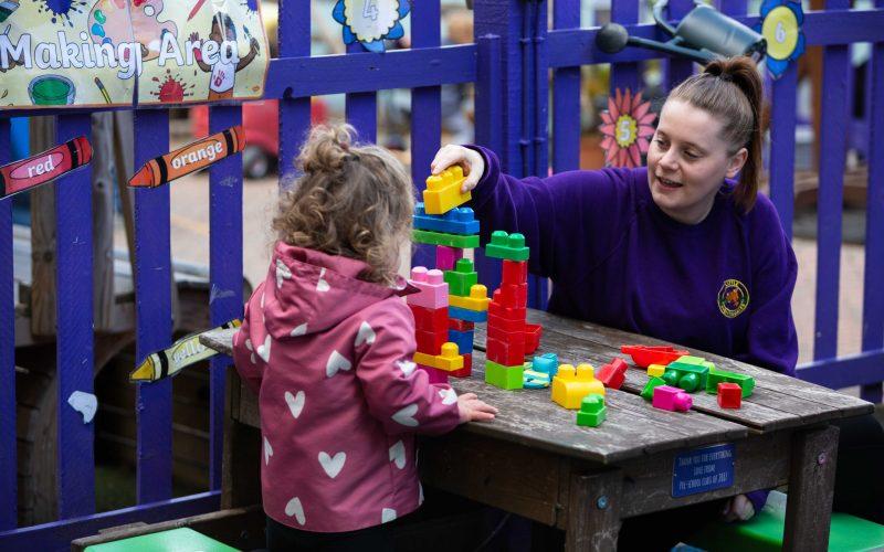 Nursery Practitoner building bricks with a child in the garden